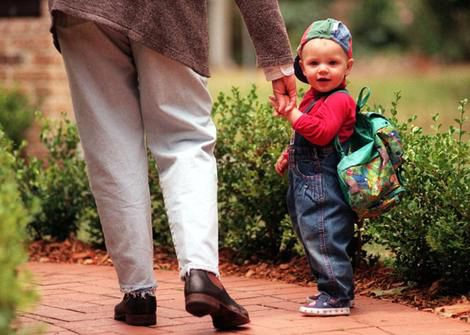A toddler holding his mother's hand as he goes to daycare.