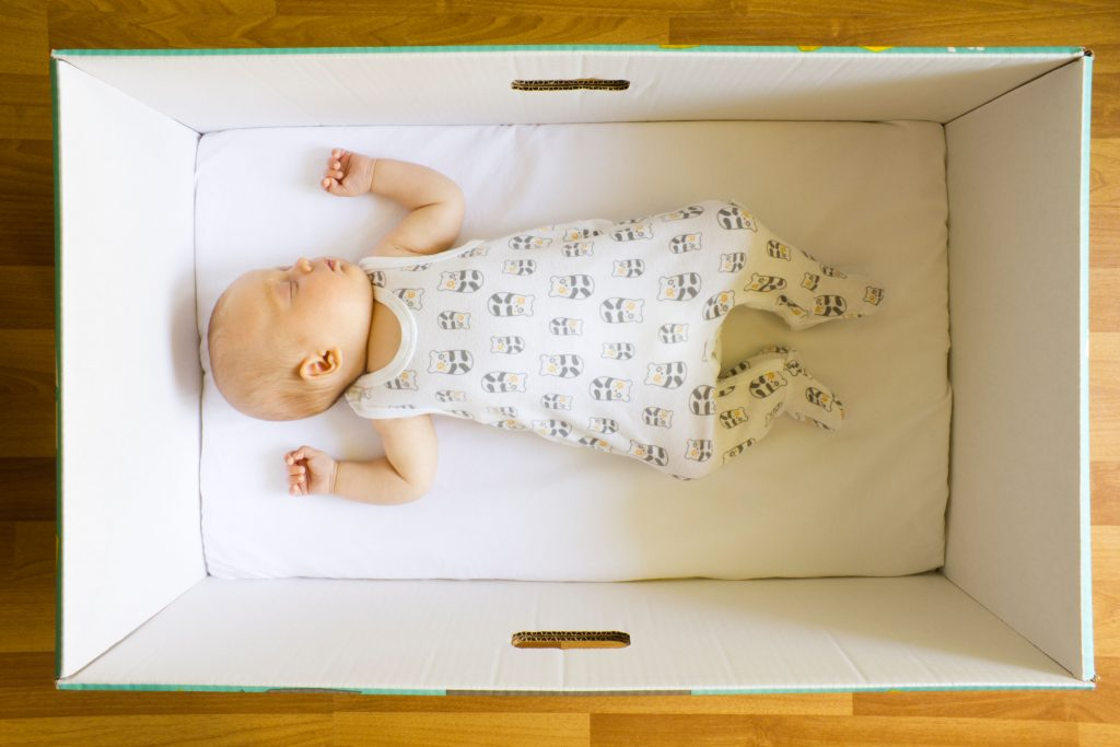 DA44YD Young baby is sleeping in a Finnish maternity box that doubles up as a crib